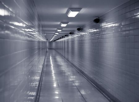 Long clean, cold looking corridor lit by fluorescent lights photo
