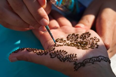 Henna tattoo painted on young womans hand photo