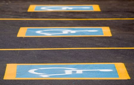 Row of parking spaces with a handicapped sign photo