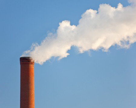 atmosphere: Tall industrial brick chimney venting gasses into the atmosphere