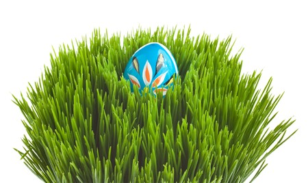 Hand painted Easter egg arranged on a grass basket photo
