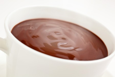 Luxurious steaming hot chocolate swirling in a cup Imagens