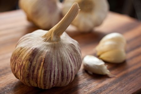 Large piece of garlic in the foreground with a couple of peeled cloves and other garlic bulbs in the background, set on a wooden cutting board photo