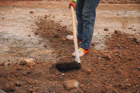 Close up of a Labour man digging soil photo