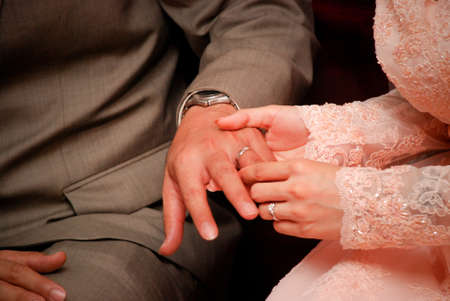 Bride putting a wedding ring on