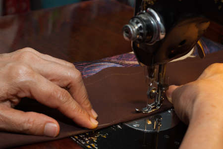 old woman hand using sewing machine
