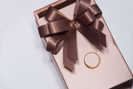 Gold ring on luxury gife box with brown ribbon