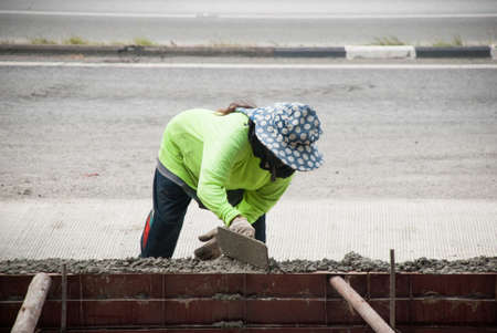 A workers hand holding plastering tool to build a footpath near the road