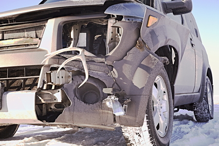 collisions: Car front end damage from high speed collision with a large deer at night in the snow