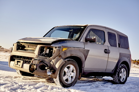 Car front end damage from high speed collision with a large deer at night in the snow