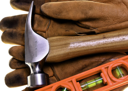 Closeup of new construction framing hammer and buble level on heavy leather work gloves photo
