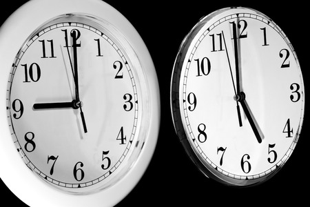 Black and White wall clocks showing the typical 9 to 5 work day photo