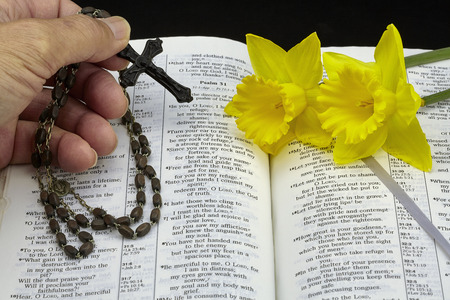 isaiah: Man holding vintage rosary with bible and flowers.jpg