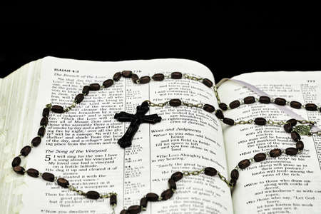 isaiah: Vintage rosary and crucifix on open bible with black background Stock Photo