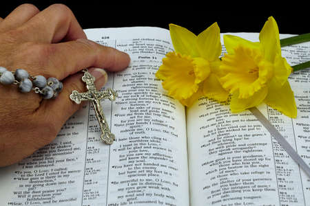 isaiah: Man with vintage rosary and yellow daffodil flowers on open bible