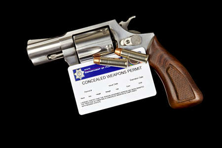 concealed: Revolver with Bullets and Concealed Weapon Permit Stock Photo