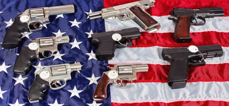 38 caliber: Pistols and revolver assorted firearms for sale on USA America flag Stock Photo