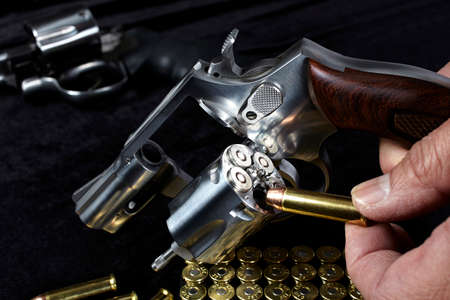 38 caliber: Man loading compact magnum revolver firearm Closeup Stock Photo