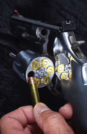 38 caliber: Man Loading Magnum Revolver Detail Closeup Gun