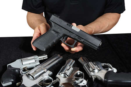 man with gun: Man displaying pistol and revolver firearms for sale Stock Photo
