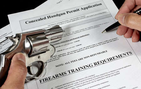 38 caliber: Man with pistol and handgun permit application Stock Photo