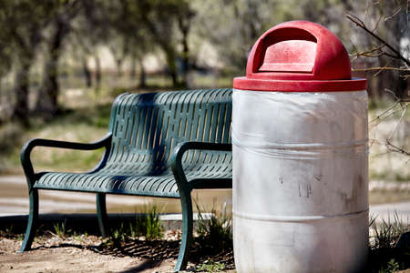 public waste: park bench and rubbish can with lid on forest trail and park Stock Photo