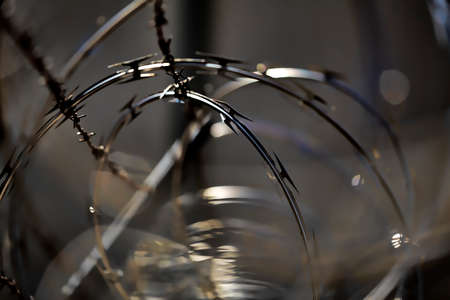 razor wire: chain link security fence with barb and razor wire closeup Stock Photo