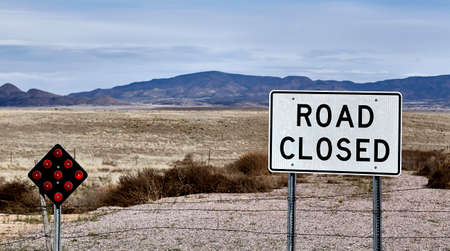 road closed: road closed street sign at end of road country landscape and mountains