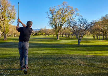 golfcourse: senior retired man with irons and putter on golf course