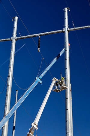 power line transmission: high voltage power line transmission tower workers with crane and blue sky