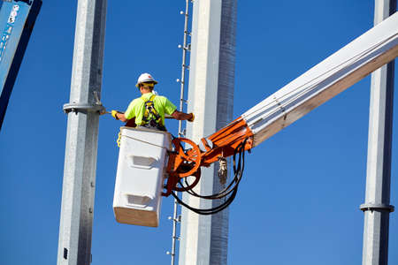 power line transmission: high voltage power line transmission tower workers with crane high boom lifts and blue sky