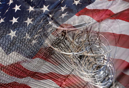 naturalization: USA Border fence barb razor wire with American Flag Immigration Concept photograph