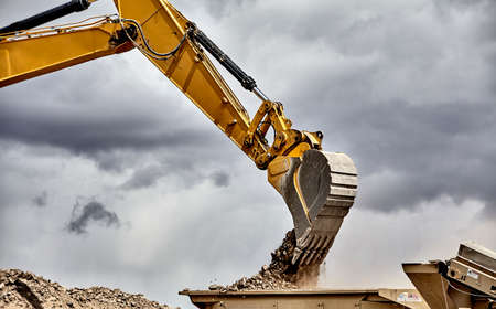 jobsite: Construction industry heavy equipment excavator moving gravel at jobsite quarry with stormy skies