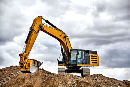 heavy equipment: Construction industry heavy equipment excavator moving gravel at jobsite quarry with stormy skies