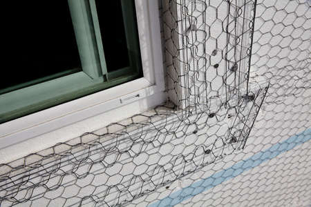 stucco house: Home building industry house window sill stucco mesh installation closeup