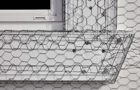 stucco house: Home building industry house window frame stucco mesh installation closeup