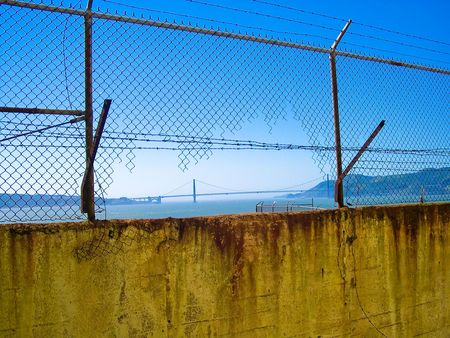 Golden Gate bridge seen through Alcatraz chain link fence photo