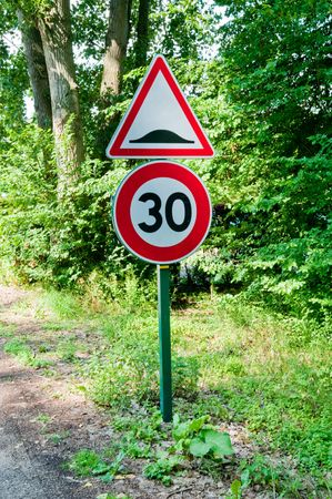 Speed limit and speedbump road sign photo