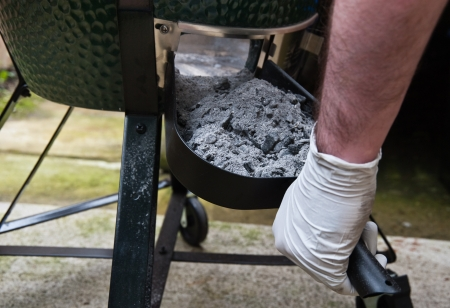 Sweeping charcoal ash out of bbq Stock Photo - 14300936