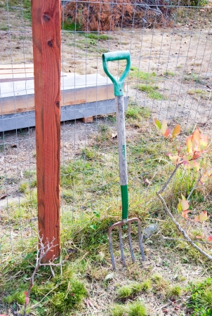 hayfork: Rusty old pitchfork leaning against a fence Stock Photo