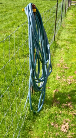 Water hose hanging on a farm fence