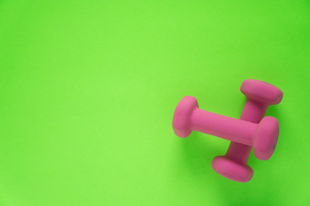 Fitness equipment with womens pink weights/ dumbbells isolated on a lime green background with copyspace (aka empty text space). Stock Photo
