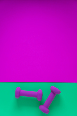 Fitness equipment with womens purple weights/ dumbbells isolated on a teal green and fuschia magenta background with copyspace (aka empty text space).