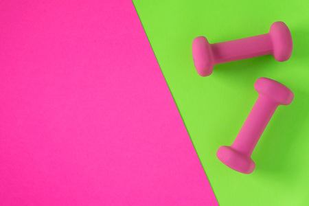Fitness equipment with womens pink weights/ dumbbells isolated on a lime green and hot pink background with copyspace (aka empty text space). Stock Photo