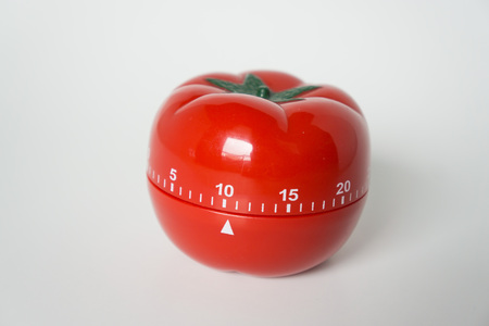 Close up view of mechanical tomato shaped kitchen clock timer for cooking and studying. Used for pomodoro technique for time and productivity management. Isolated on white background, at 10 minutes.