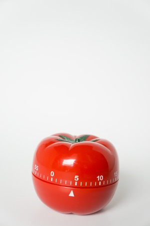 Close up view of mechanical tomato shaped kitchen clock timer for cooking and studying. Used for pomodoro technique for time and productivity management. Isolated on white background, at 5 minutes.