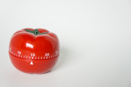 Close up view of mechanical tomato shaped kitchen clock timer for cooking and studying. Used for pomodoro technique for time and productivity management. Isolated on white background, at 15 minutes.