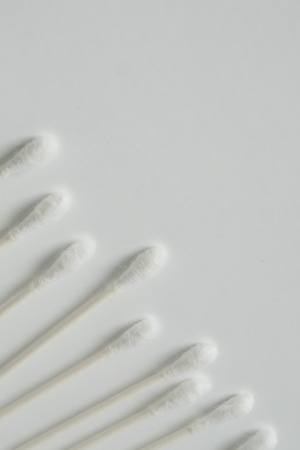 Q tip, or cotton bud swab top view on vertical white background with blank empty space for copy or text; Features best health care hygiene practices to clean ear.