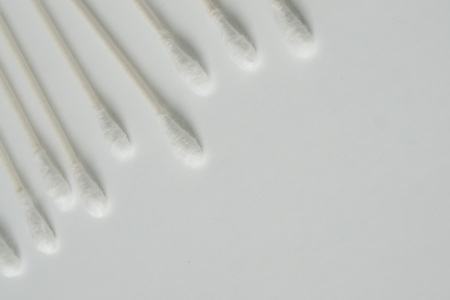 Q tip, or cotton bud swab top view on horizontal white background with blank empty space for copy or text; Features best health care hygiene practices to clean ear.