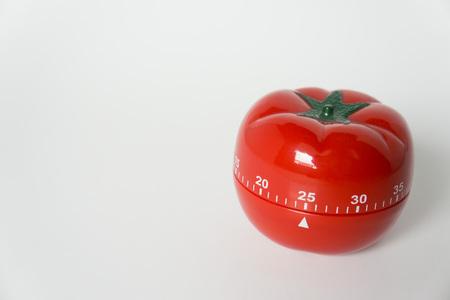 Zamknij widok mechanicznego zegara kuchennego w kształcie pomidora do gotowania i nauki. Używany w technice pomodoro do zarządzania czasem i wydajnością. Pojedynczo na białym tle, co 25 minut.